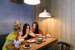Three young cute girl girlfriends chatter, gossiping, share secr Stock Images