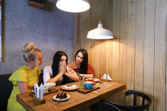 Three young cute girl girlfriends chatter, gossiping, share secr Stock Photos