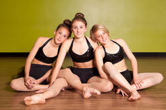 Three young dancers. Portrait of three young dancers sat together in a studio Royalty Free Stock Image