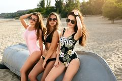 Three young fashionable lovely women relaxing on the beach in the sun. Pretty happy suntanned models wearing hot bikini Royalty Free Stock Photography