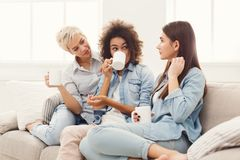Three young female friends with coffee chatting at home. Diverse female friends at home. Three young women with coffee cups chatting on sofa, gossiping and stock photo