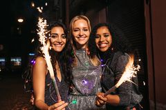 Three young female friends enjoying new years eve. With fireworks at night royalty free stock photo