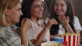 Three young female friends laughing while watching a movie together stock photo
