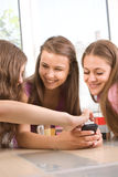 Three young female friends smiling stock images
