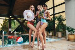 Three young female models posing in swimsuits holding pineapples, hat and juice at swimming pool at spa center Stock Photo