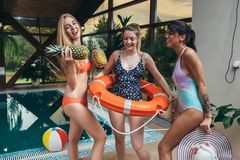 Three young female models posing in swimsuits holding pineapples, hat and juice at swimming pool at spa center.  Stock Photo