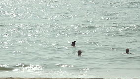 Three young female swimming in the ocean stock video