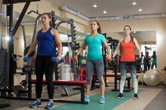 Three young fitness active girls doing exercises with kettlebells in gym. Royalty Free Stock Photos