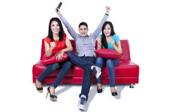 Three young friends cheering at television Royalty Free Stock Photos