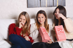 Three young friends eating popcorn and watching movies. Stock Photography