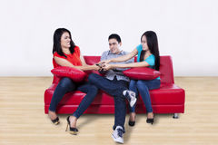 Three young friends fighting for a remote Stock Photography