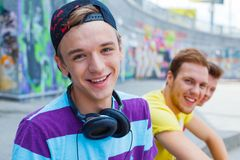 Three young friends happy. Portrait of happy teens boy with his friends by painted wall looking at camera Stock Photos