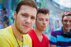 Three young friends happy. Portrait of happy teens boy with his friends by painted wall looking at camera Stock Image