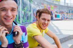Three young friends happy. Portrait of happy teens boy with his friends by painted wall looking at camera Stock Images