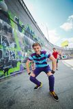 Three young friends happy. Happy teens boy with his friends by painted wall looking at camera. Vertical view Stock Photography