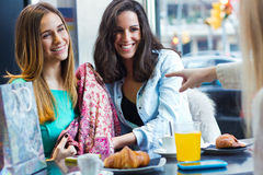 Three young friends having breakfast on a morning shopping in th Royalty Free Stock Photography