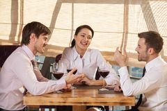 Three young friends having wine together in cafe. Stock Photos