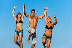Three young friends holding hands jumping. Royalty Free Stock Photos