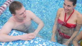 Three young friends laughing and talking in the swimming pool stock video footage