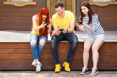 Three young friends laughing watching video on mobile phone outd. Oors.Friendship, internet addiction, wireless technologies royalty free stock images