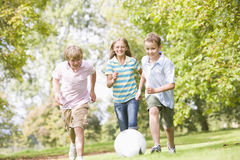 Three young friends playing soccer stock photos