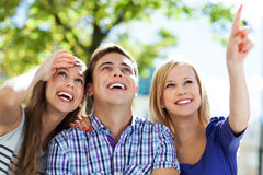 Three young friends pointing. Portrait of young people outdoors Royalty Free Stock Images