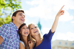 Three young friends pointing. Portrait of young people outdoors Stock Photos