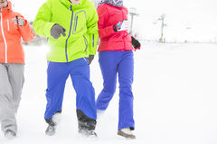 Three young friends running in snow Royalty Free Stock Images