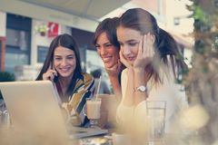 Three young friends shopping online in cafe on laptop. Three young friends have fun and shopping online in cafe on laptop.Lifestyle royalty free stock image