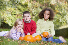 Three young friends sitting on grass with pumpkins royalty free stock photo