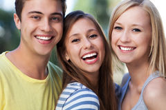 Three young friends smiling. Portrait of young people outdoors Royalty Free Stock Images