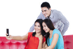 Three young friends taking photo by mobile phone Royalty Free Stock Image