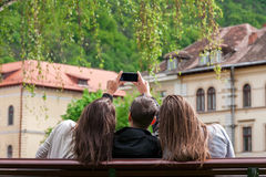 Three young friends taking photos with smartphone in the park Royalty Free Stock Photography