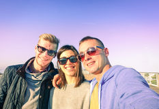 Three young friends taking selfie on sunny autumn day. Fashion  and hipsterstyle concept - Warm light filter look Stock Images