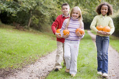 Three young friends walking on path with pumpkins Royalty Free Stock Photos