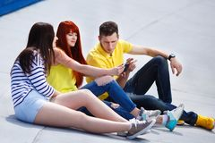 Three young friends watch movie premiere on mobile phone outdoor royalty free stock photography
