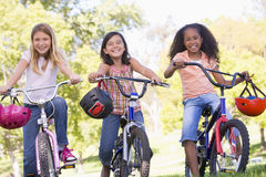 Three young girl friends on bicycles smiling royalty free stock images