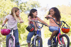 Three young girl friends on bicycles smiling stock photos
