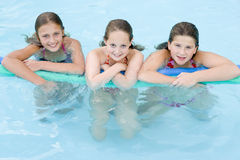 Three young girl friends in swimming pool Royalty Free Stock Image