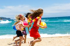 Three young girlfriends running on beach. Stock Images