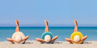 Three young girls on the beach wearing straw hats in the colors of the flag of Canary Islands.