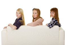 Three young girls - classmate on couch Royalty Free Stock Photos