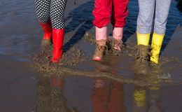 Girls in gumboots walking in puddle. Three young girls in colorful gumboots walking in puddle. Shoes for extreme rainy weather conditions Royalty Free Stock Images