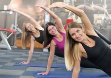 Three young girls doing a plank on exercise mat at gym. Group training. Healthy lifestyle concept stock images