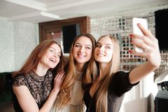 Three young girls are doing selfie photo in a restaurant. royalty free stock photography