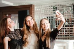 Three young girls are doing selfie photo in a restaurant. royalty free stock images