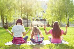Three young girls doing yoga pose outdoor, yoga at sunset in the park, back view.  royalty free stock image