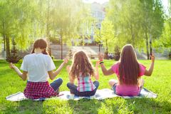 Three young girls doing yoga. Pose outdoor, yoga at sunset in the park, back view royalty free stock photography