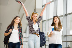 Three young girls go with their luggage at the airport and laugh. A trip with friends Royalty Free Stock Photo