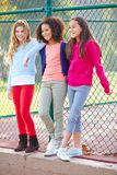 Three Young Girls Hanging Out Together In Park Stock Photo